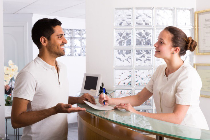 lễ tân đang bám sát checklist dịch vụ khách sạn